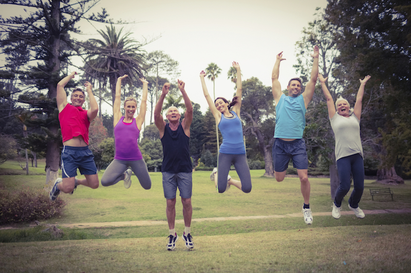 outdoor fitness class jumping for joy celebrate reaching their goals