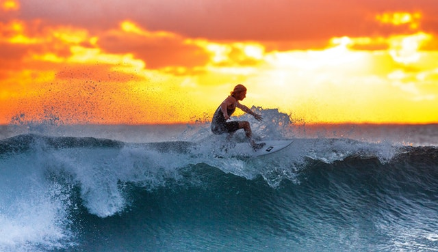 woman surfing in the sunset