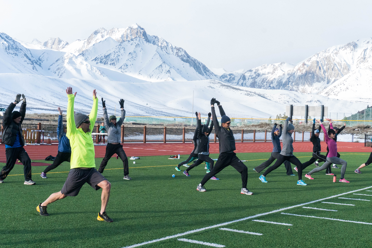 Mammoth Track Club members stretching in front of snowy mountains